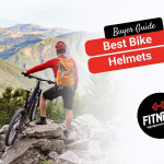 man wearing a bike helmet at the top of a summit looking over the mountains