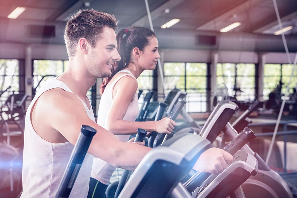 man and woman on two ellipticals in the gym