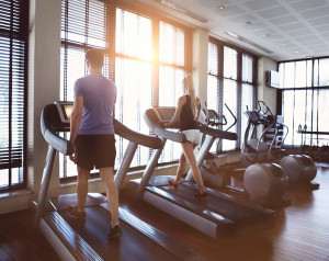 Couple in gym working out on treadmills