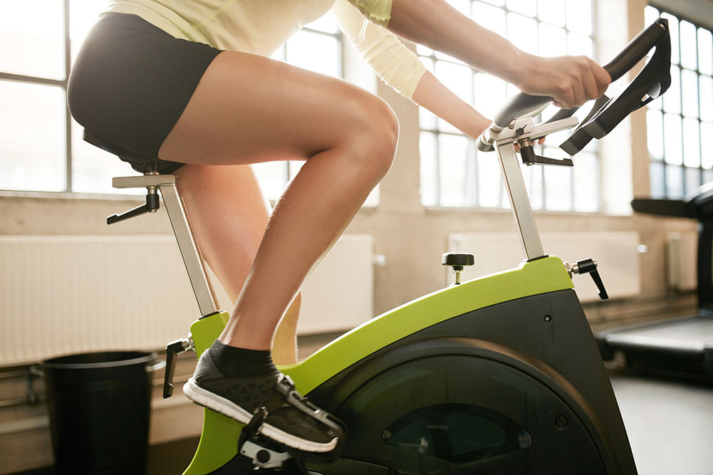 woman on a green and black spin bike in a gym
