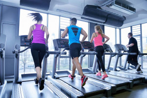 Four people running on treadmills in a gym