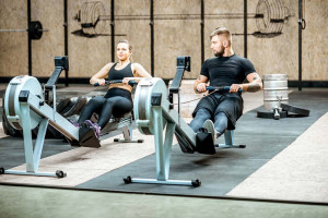 Couple on rowing machines in the gym
