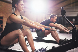 woman using a rowing machine and man in background using one also