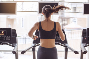 woman running on a treadmill from behind, pony tail swishing