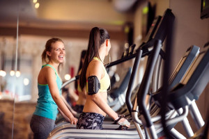 Two young women on treadmills smiling at each other