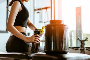 strong woman preparing preworkout supplement