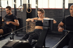 female and two males using rowing machines