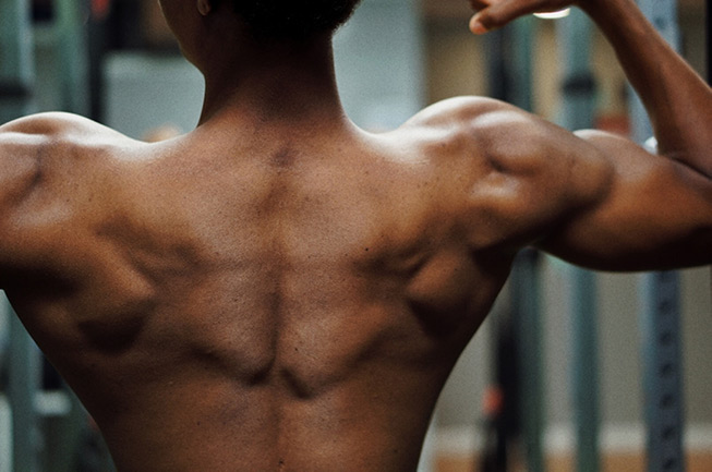 man flexing back and shoulder muscles