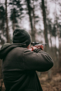 hunter in the forest pointing gun