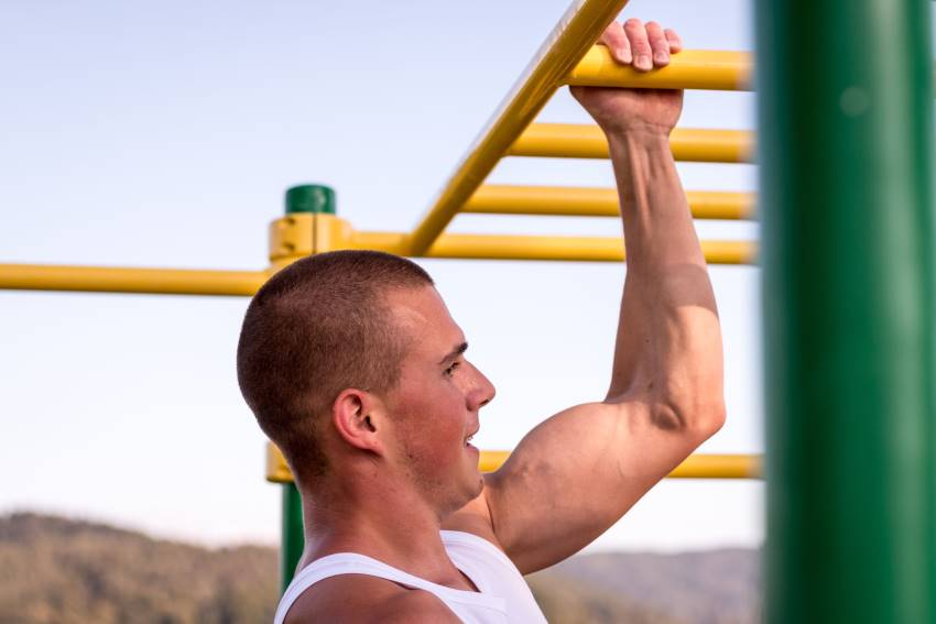 Man doing one arm pull up