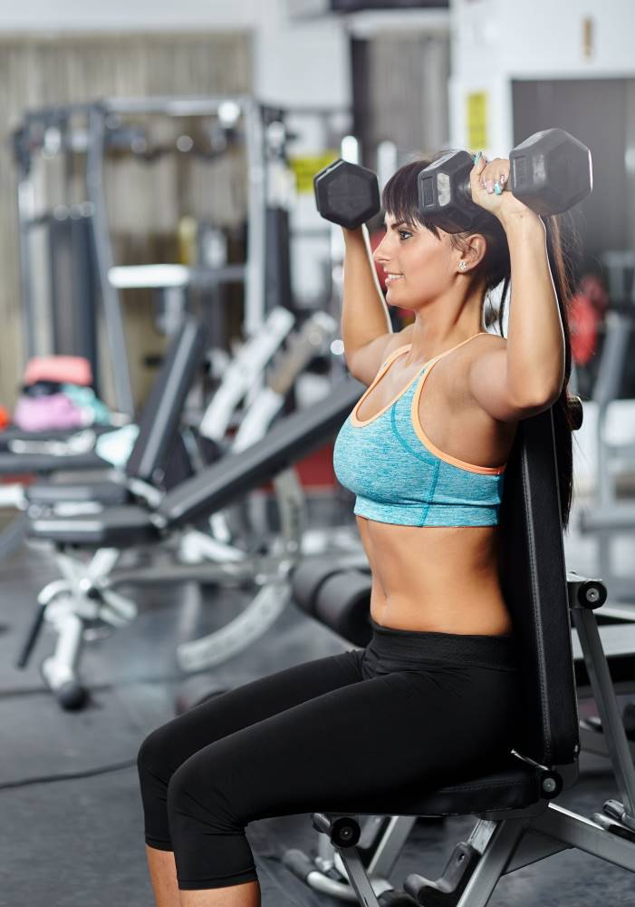 woman doing seated dumbbell shoulder press