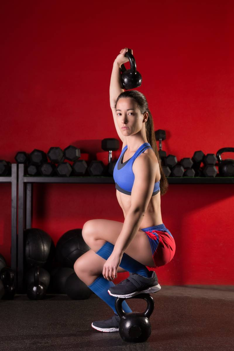 woman holding a kettlebell above head