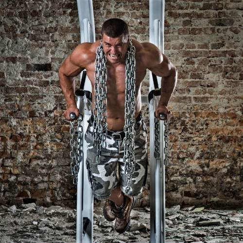 Man doing dips with heavy chains