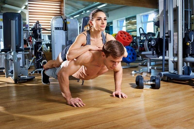 Man doing push up with a woman on his back
