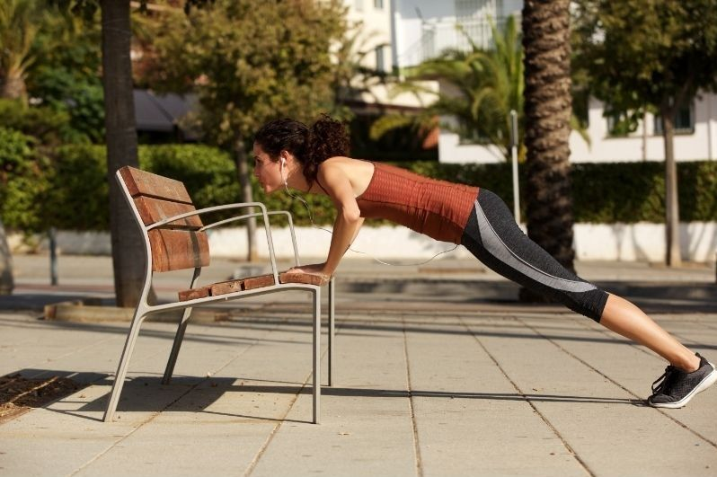 Woman doing angled push ups on a chair