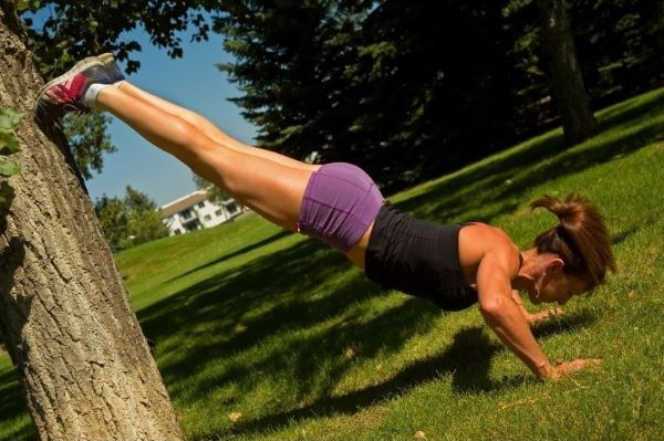 Woman doing decline push ups on a tree