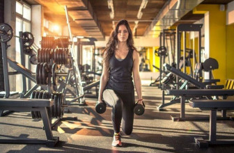 Woman lunging with dumbbells in a gym