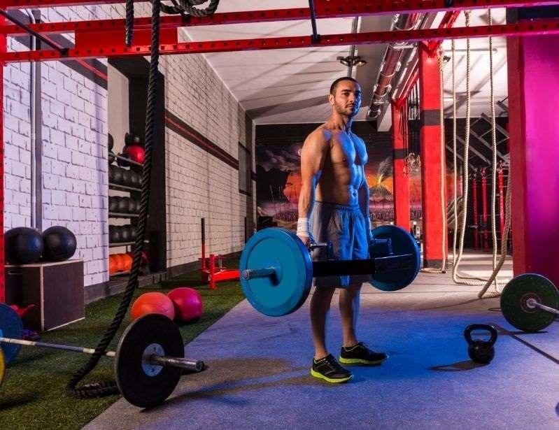 man holding trap bar in gym