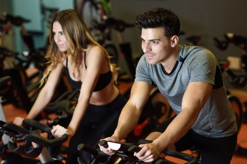 Couple doing spin bike routine