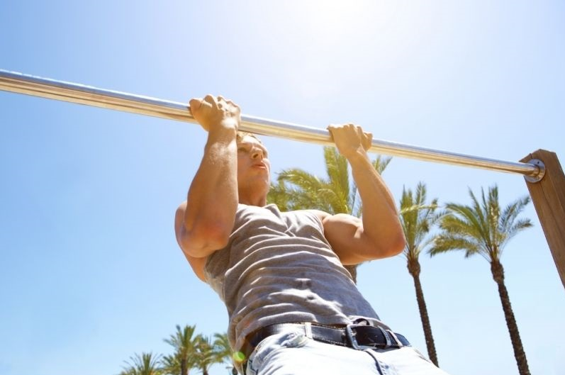 Man doing pull ups in the sun outside